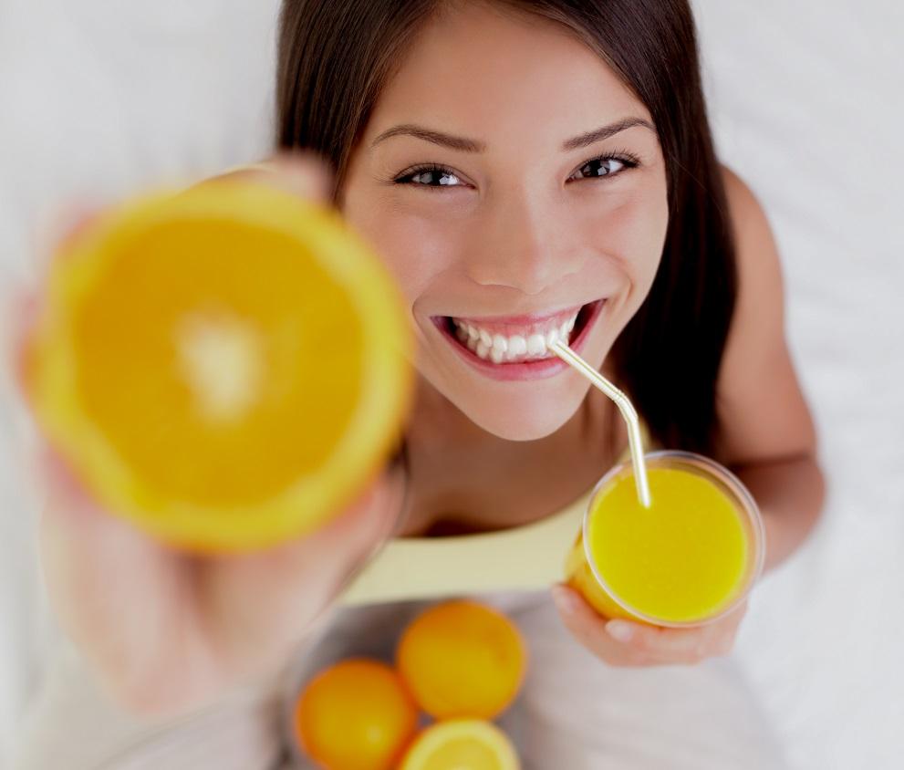Woman drinking orange juice smiling showing oranges. Young beautiful mixed-race Asian / Caucasian model.